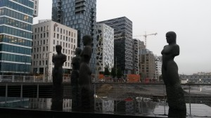 "These are statues in front of the area called ""barcode"" in downtown Oslo. Notice the buildings in the background? They are of dissimilar size and design, hence the name barcode. Most find them to be architecturally interesting, but I find them annoying."